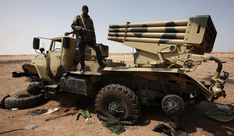 A rebel stands on a wrecked missile launcher after air strikes on the western outskirts of of the town of Ajdabiyah