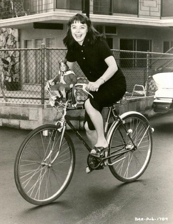 Janet Munro and King Brian ride a bike.jpg