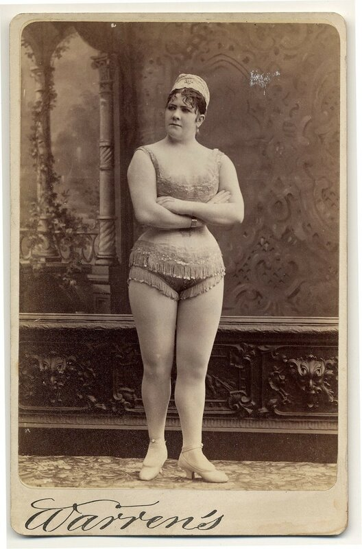 1890. Viola Clifton facing front in sleeveless short fringed top and short fringed trunks.