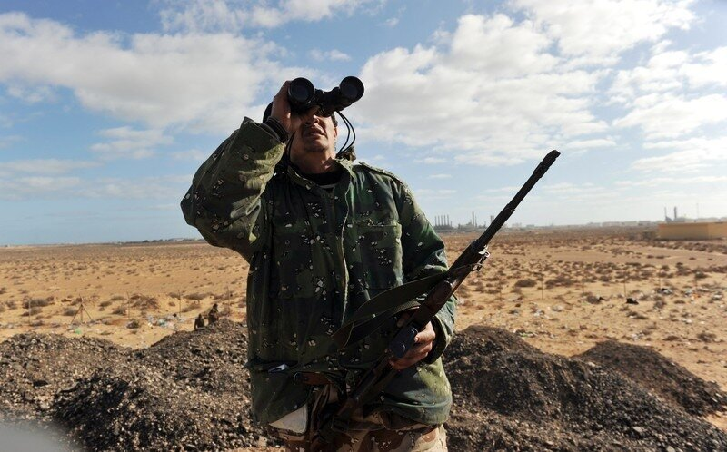 A Libyan rebel fighter scans the sky as