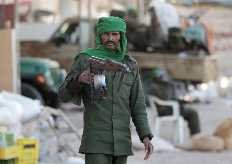 A Libyan soldier loyal to leader Muammar Gaddafi standing in a street strewn with rubble in the city of Misrata