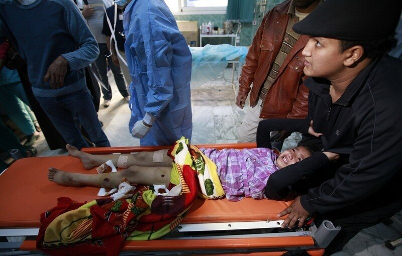 Ten-year-old Mabrok from Brega grabs onto relative's clothing as she cries in pain while waiting to have shrapnel wounds to her legs dressed by medical staff at Ajdabiyah hospital