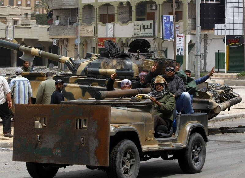 Rebel fighters drive a makeshift armoured jeep past a captured Gaddafi forces tank in Tripoli street