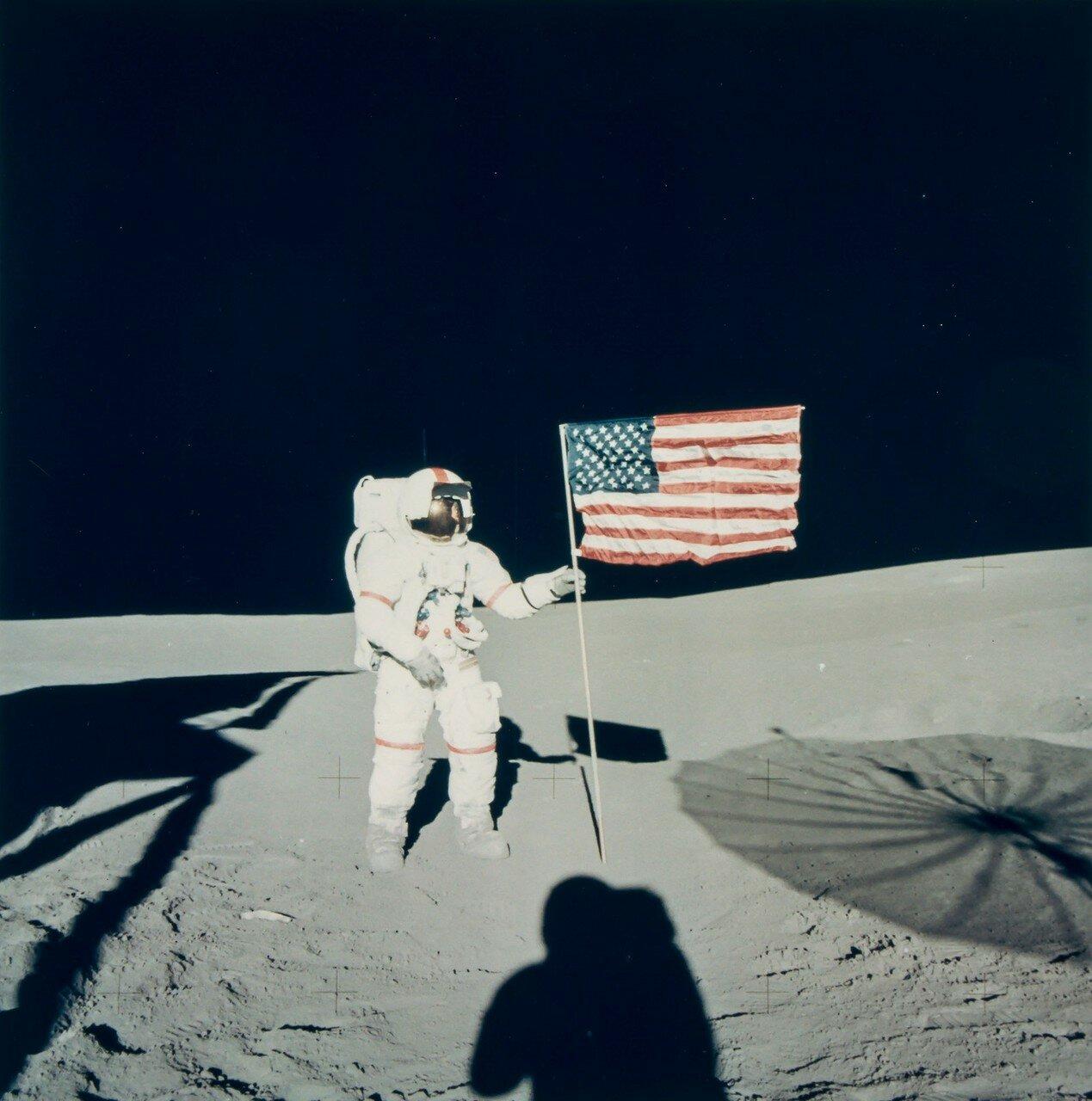 Шепард у флага на проволочном каркасе. Видны тени от лунного модуля и развёрнутой антенны