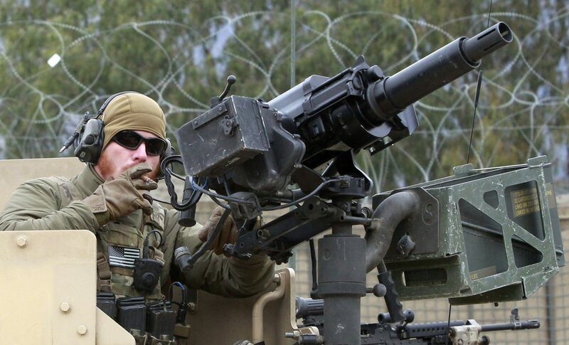 Member of the U.S. military's Special Forces smokes cigar while holding weapon as his unit leaves for mission at Forward Operating Base Joyce in Kunar province