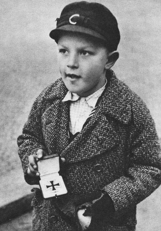 Немецкий мальчик-сирота меняет Железный крест своего отца на сигареты. Берлин,  Британская зона оккупации. 1945 год.