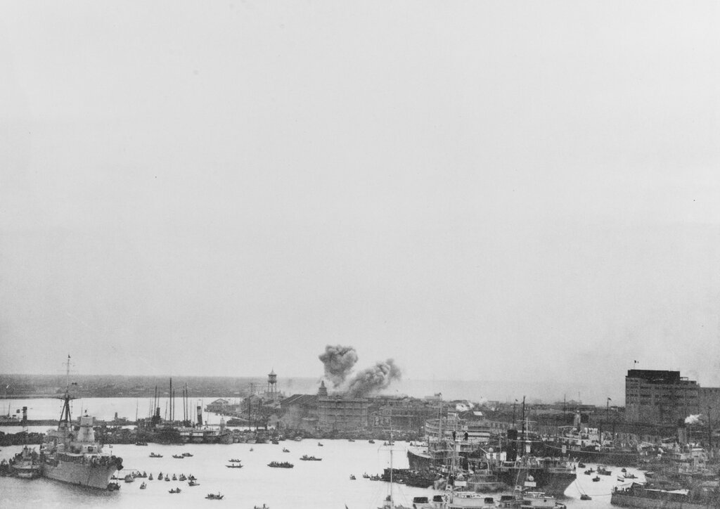 Shanghai, China. View taken from USS AUGUSTA (CA-31) showing bombs bursting in Nantao, the southern suburb of Shanghai, on 10 November 1937. Italian cruiser MONTECUCCOLI at bottom left of image.