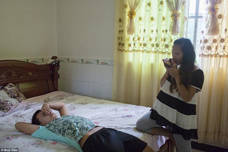 Будущая мать-подросток Мэй держит пару маленьких ботинок для ребенка, а ее муж Цзянь лежит на кроват