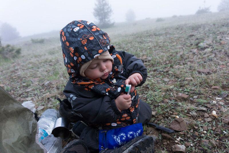 годовалый ребенок играет в тумане у палатки в походе