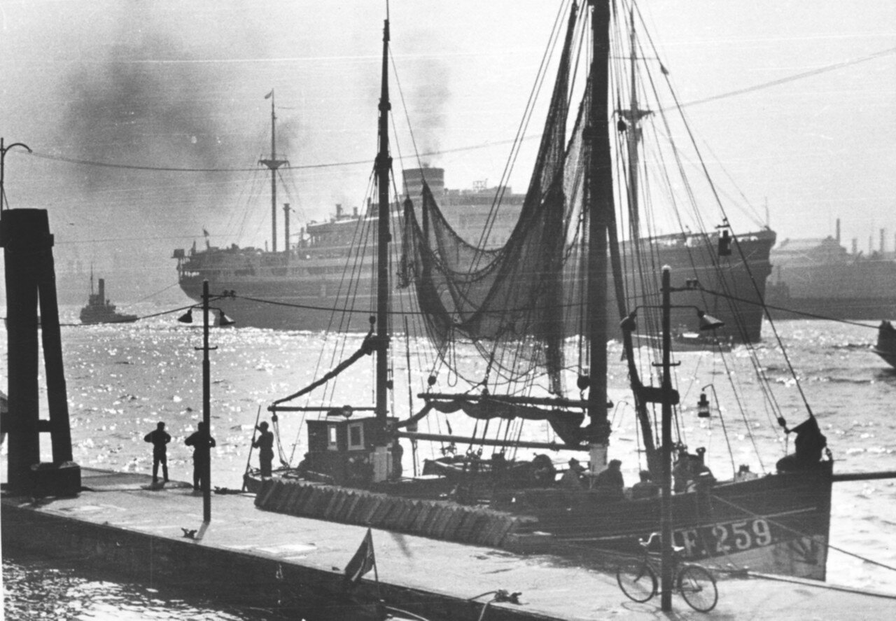 Гамбург. Японский пароход выходит из гавани. На переднем плане рыболовное судно на причале