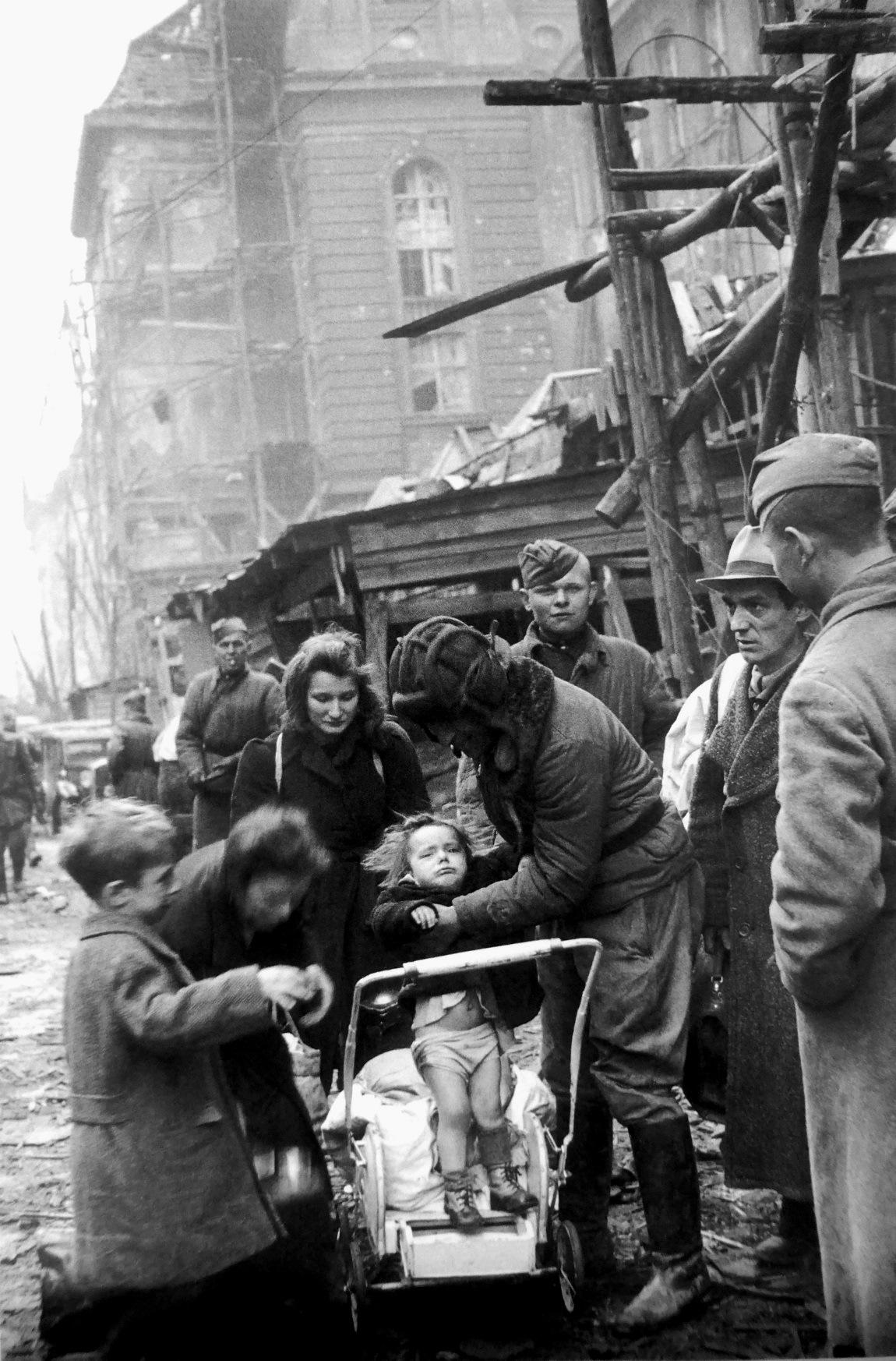 Советский солдат помогает немецкой женщине с детьми. Берлин, май 1945 года.