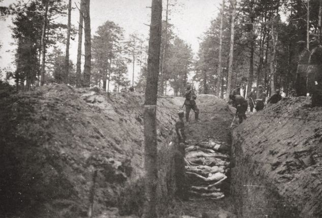 A mass grave in which the corpses of Soviet POWs are being buried.jpg