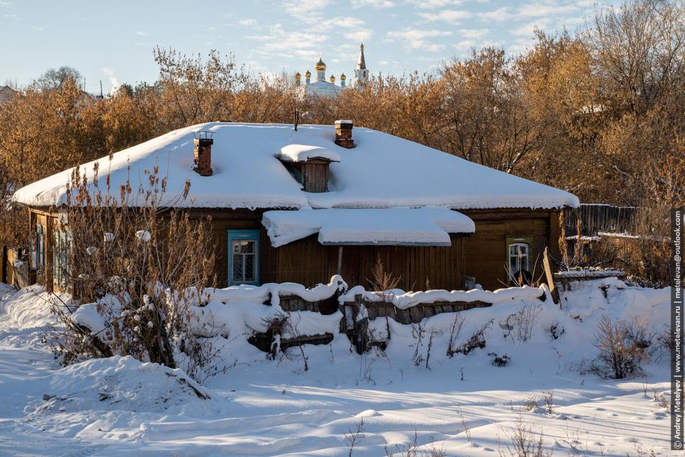 старый деревянный дом, а на заднем плане церковь