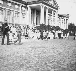 Гуляющие перед фасадом дворца