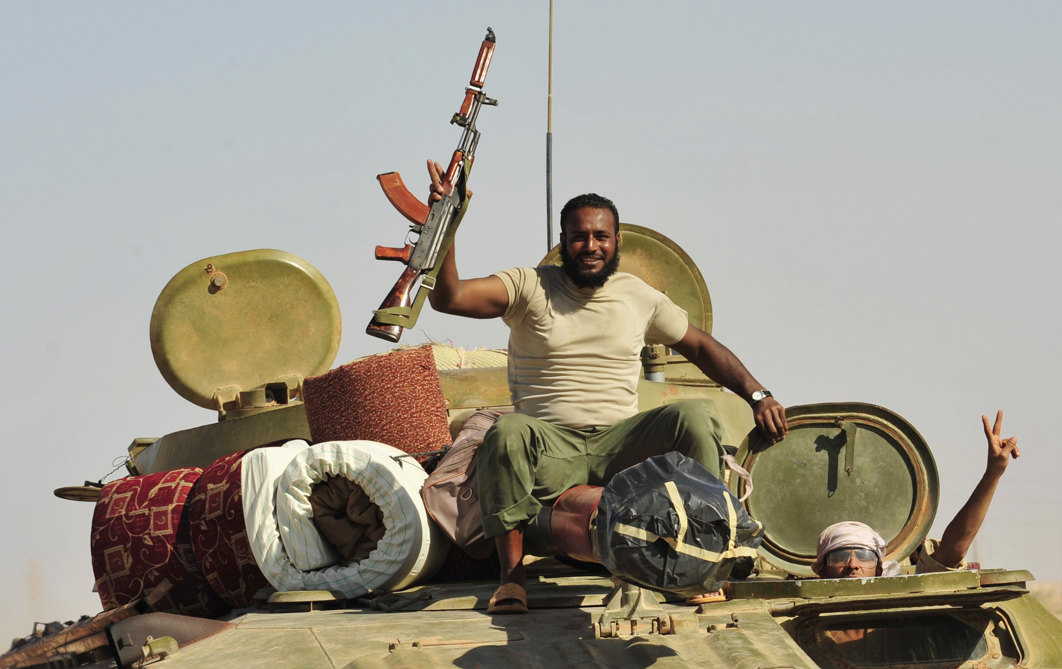 Libyan rebels make their way in a tank passing through the area of Bin Jawad to the city of Sirte