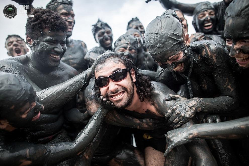 Участники карнавала Bloco da Lama обмазывают новоприбывшего грязью из озера Жабакуара,Парати,ш