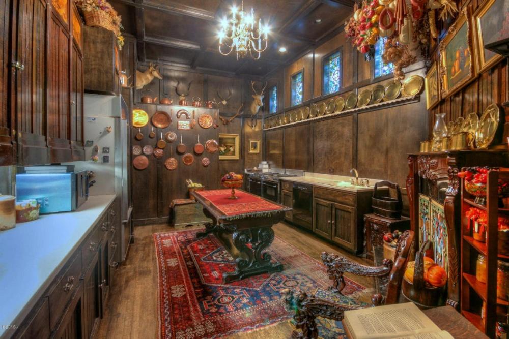 Кухня протяженностью около 13,7 метров обшита панелями изберезового дерева. Вцентре стоит библиоте