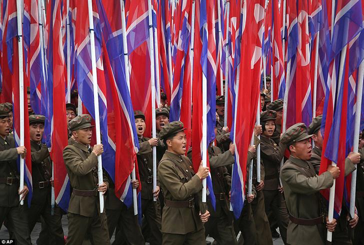 Участники парада в военной форме несут национальные флаги Северной Кореи.