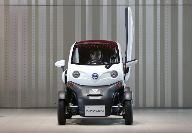 A man sits inside Nissan Motor Co's New Mobility concept car displayed at the company's sh