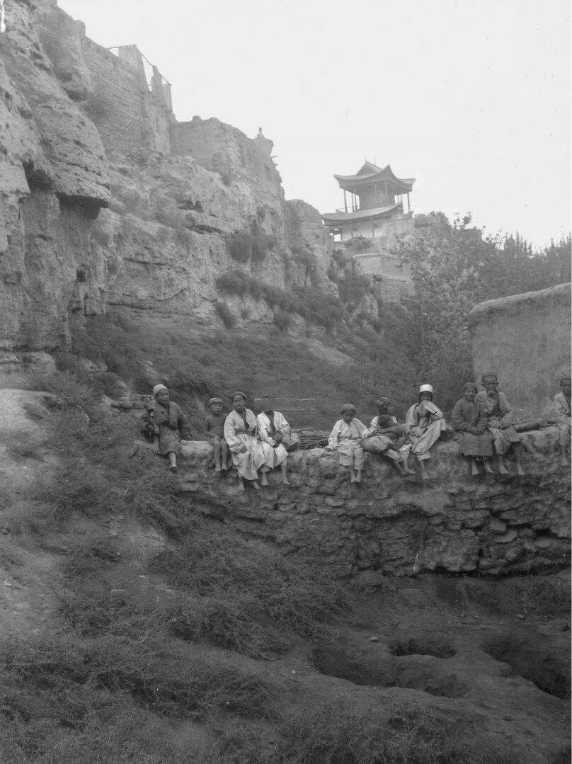 Дети сидят на каменном заборе