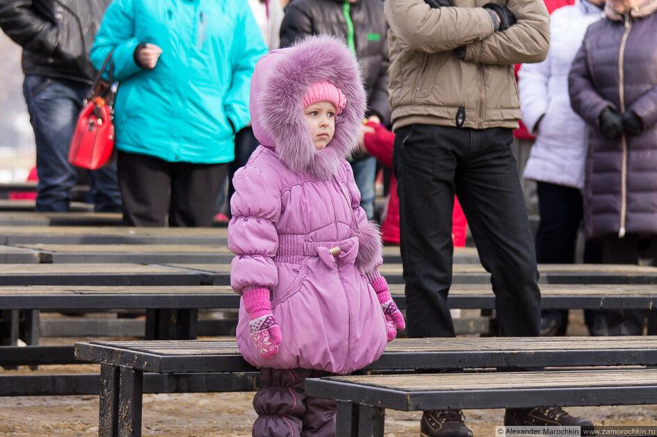 Девочка стоит и смотрит концерт на праздновании Масленицы