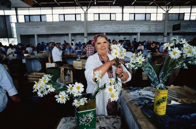 Women Holding Flowers at a Market
