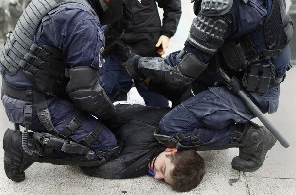 A protester is detained by the special