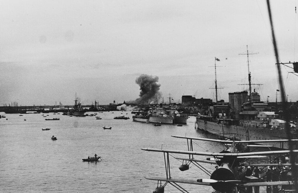 Shanghai, China. View looking upriver towards the Chinese suburb of Nantao, south of the International Settlement in Shanghai. Smoke is from Japanese bombardment. Ships in the river are (from left to right): RAIMONDO MONTECUCCOLI (Italian cruiser), DUMONT D'URVILLE and SAVORGNAN DE BRAZZA (French sloops), and HMS CUMBERLAND (British cruiser). Note Curtiss SOC aircraft on the USS AUGUSTA's (CA-31) catapult in the foreground and Vice Admiral's pennant at the mainmasthead of CUMBERLAND, circa the fall of 1937.