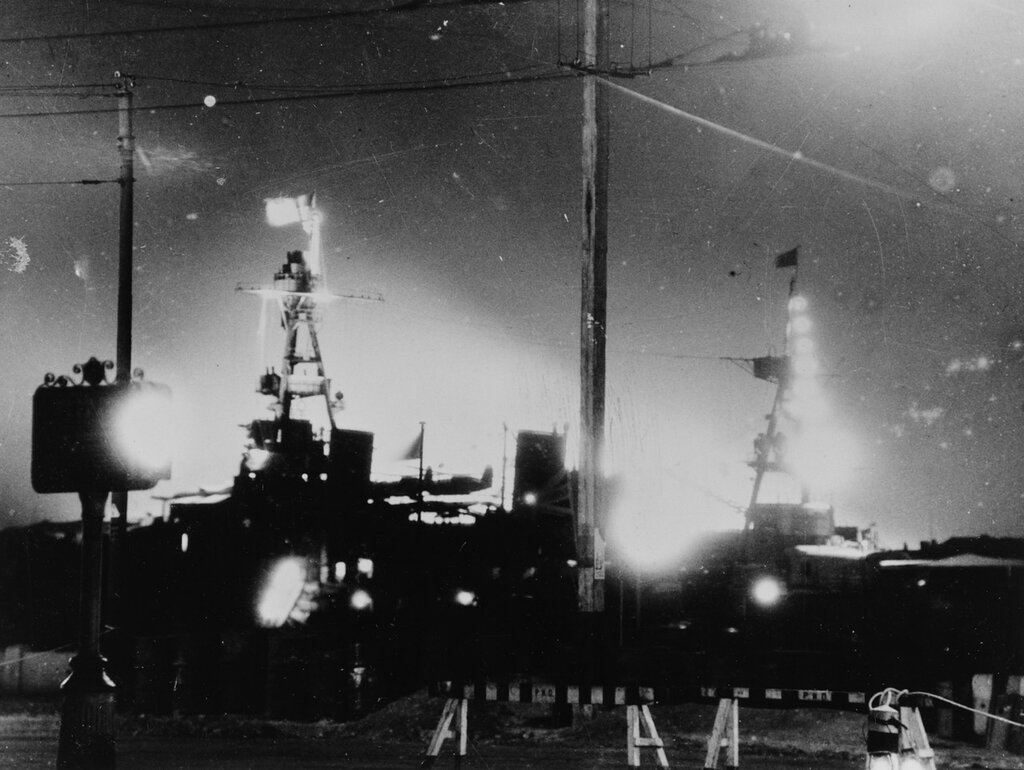 Shanghai, China. USS AUGUSTA (CA-31) silhouetted by fires on Pootung Point, circa August 1937. Note searchlight illumination of U.S. flag at foremast for identification purposes.