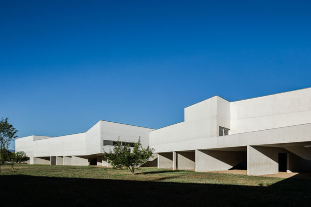 The building is built with apparent structural white concrete walls; the roof is covered almost comp