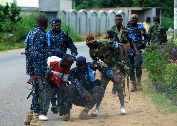 Rebel soldiers of Ivory Coast opposition leader Alassane Ouattara help their wounded comrade during a clash with Ivorian forces at Golf hotel in Abidjan