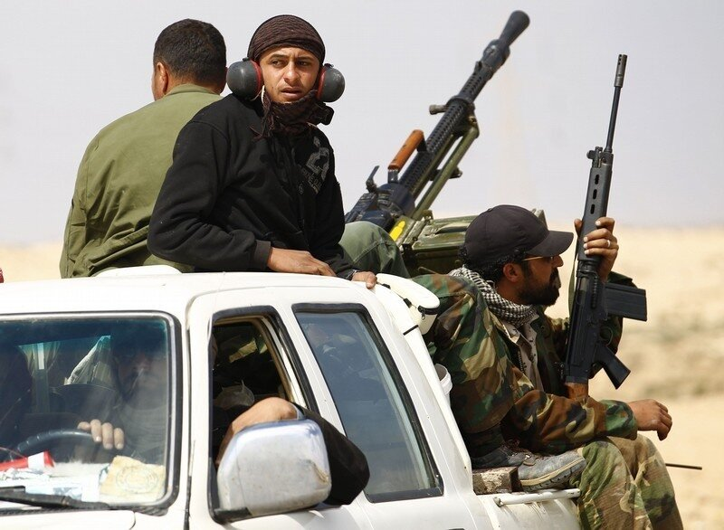 Rebel fighters ride a pick-up truck as they retreat from the frontline on the road to the east of Brega, in Libya