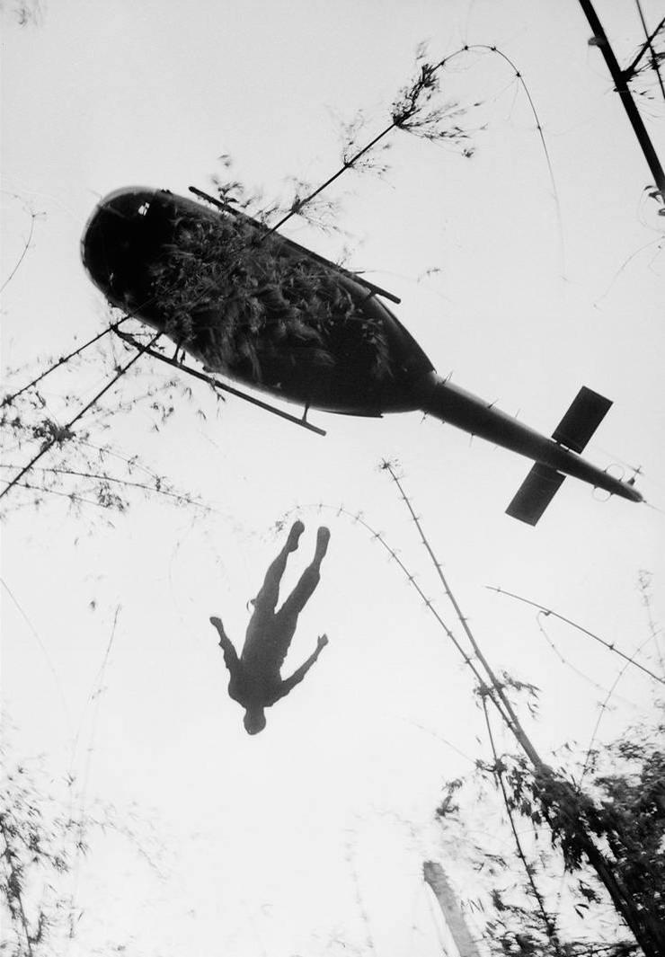 Тело американского солдата, который погиб в бою в джунглях недалеко от Камбоджийской границы, поднимают на зависший над землей вертолет в целях его последующей эвакуации