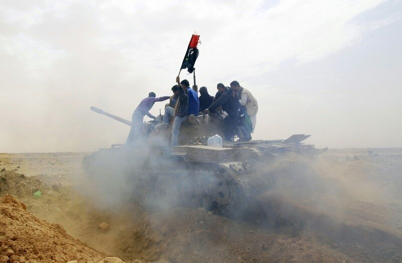 Rebels ride on top of a tank on the outskirts of Ajdabiya, on the road leading to Brega