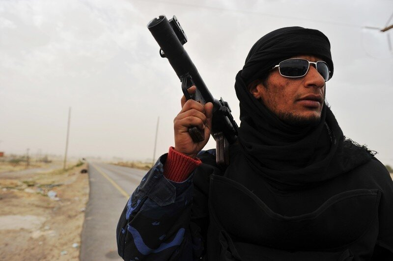 A Libyan rebel fighter holds up rocket a