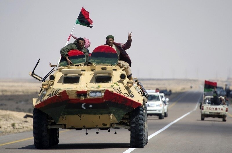Libyan rebels ride on an armoured person