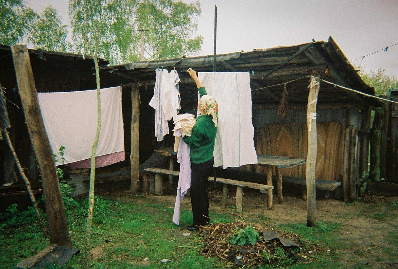 Женщина сушит белье в своем саду возле зоны отчуждения