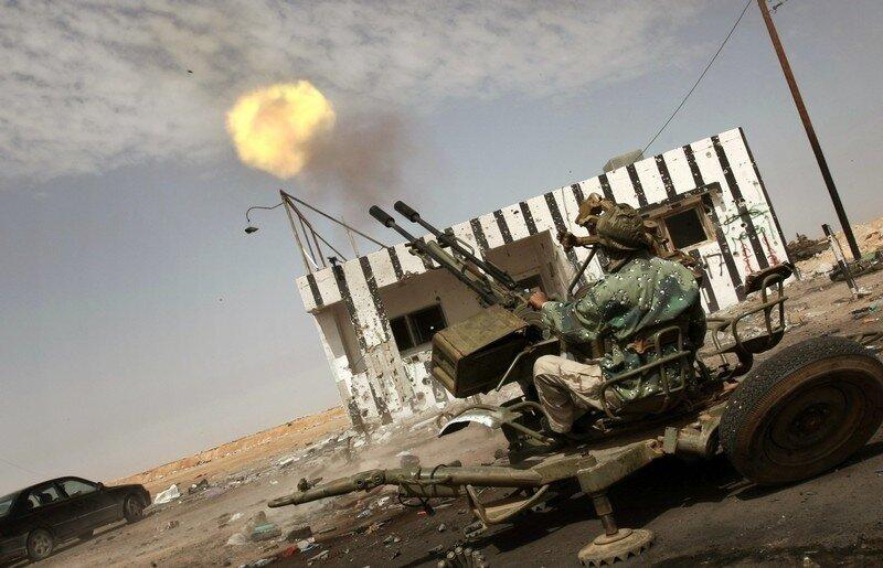 A Libyan rebel shots an anti-aircraft ma