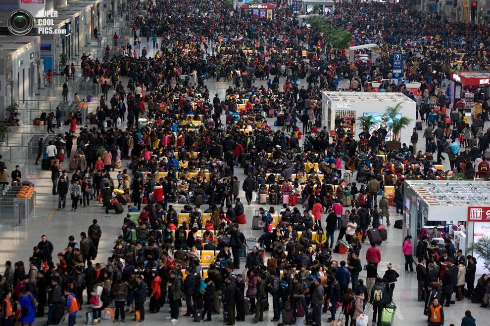 Пассажиры толпятся в зале ожидания железнодорожной станции Хунцяо, Шанхай, Китай. Сотни миллионо