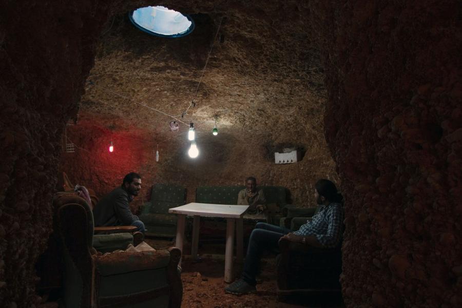 19. Бывший бурильщик скважин Абу Амер (в центре) со своей семьёй в подземном доме на окраине Алеппо,