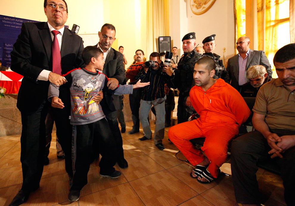 31. Мальчика уводят от боевика, которого обвиняют в убийстве его отца во время сектантской резни в 2