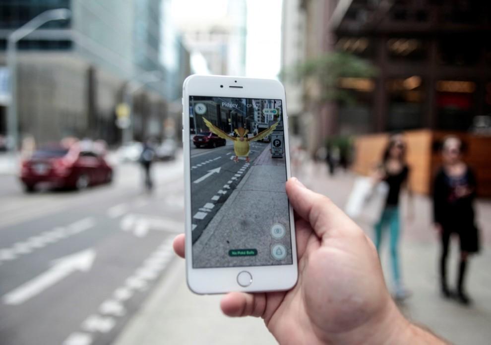 Мужчина (в центре) играет в Pokemon Go на улице возле Центрального вокзала в Нью-Йорке, США, 11 июля