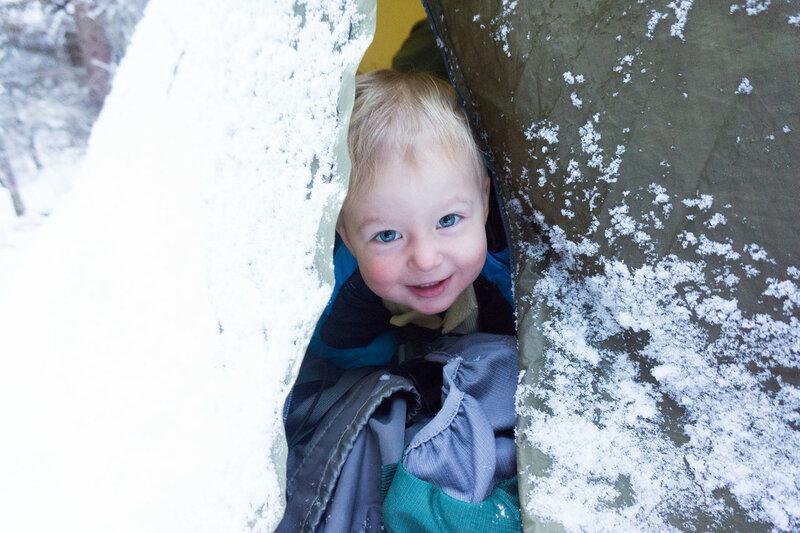 ребенок в палатке в лесу в походе зимой