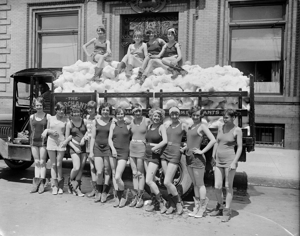Promotion for the Merchant's & Transfer Co. Young women smile and pose in swimming suits in front of a panel truck full of snow. between 1910 and 1930