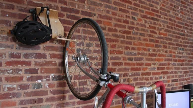 За нижний изгиб полки цепляется переднее колесо велосипеда.