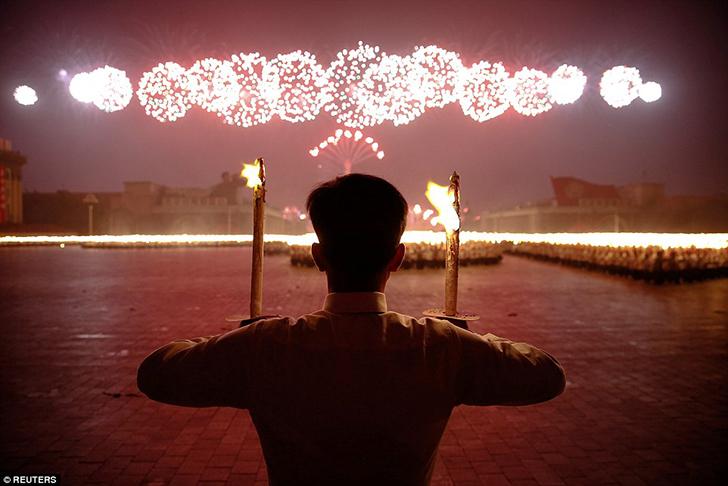 Мужчина держит факелы во время ночного шествия в Пхеньяне 9 мая. Празднование продлилось до самой но
