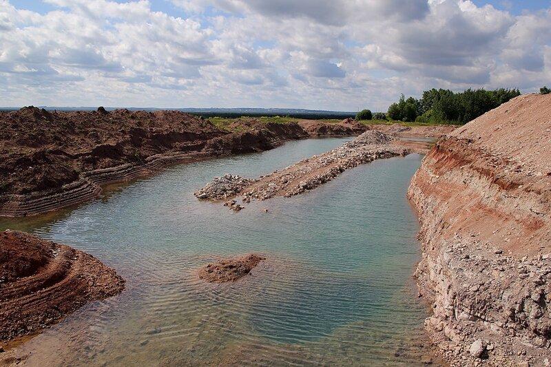 Заполненный бирюзовой водой известняковый карьер у дер. Мокины
