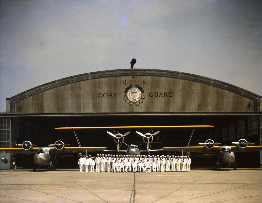 Formal portrait of U. S. Coast Guard servicemen posed in front of hangar at Floyd Bennett Field, with a Hall PH and two Grumman JRF Gooses, 1940.