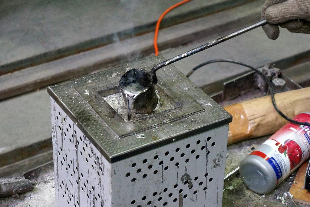 Олово рабочий зачерпывает олово и