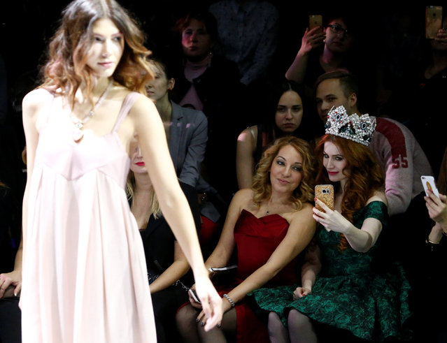 Guests take a selfie as a model presents a creation by Russian designer Elena Shipilova at the Mosco